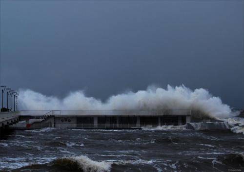 Kołobrzeskie molo zalewane przez sztormowe fale na Bałtyku