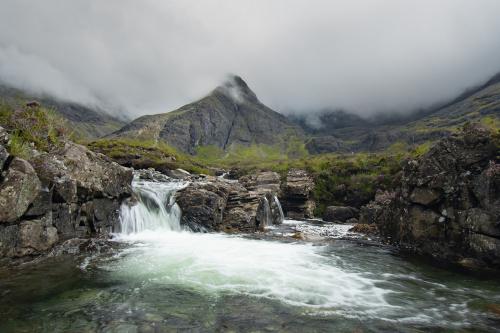 Rzeka Allt Coir a' Tairneilear i wynurzające się z mgły góry Cuillins
