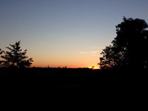 Wschód słońca nad Nowicą. Wieża kościoła po lewej